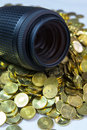 Lens and money dslr photo equipment on pile of yellow coins Royalty Free Stock Image