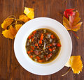 Lentil andouille soup sprouted and on an aged wooden table surrounded by fall leaves Stock Photography