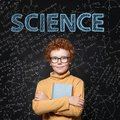 Lern Science. Clever student child on blackboard background with maths formulas Royalty Free Stock Photo