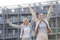 Les jeunes femmes d affaires enthousiastes avec des bras ont augmenté contre l immeuble de bureaux Photographie stock