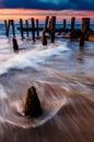 Les vagues tourbillonnent autour des empilages de pilier dans la baie de delaware au coucher du soleil s Image stock