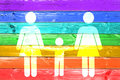 Lesbian family with child white sign on a rainbow gay flag wood planks background Royalty Free Stock Photo