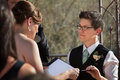 Lesbian partners reading marriage vows in ceremony Stock Photos