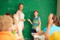 At the lesson portrait of smart teacher and schoolgirl standing by blackboard and looking schoolkids in classroom Royalty Free Stock Image