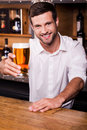Let me quench your thirst handsome young male bartender in white shirt stretching out glass with beer and smiling while standing Royalty Free Stock Photos