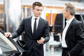 Let me show you interior of this car handsome young classic salesman standing in the dealership and helping a client to make a Stock Image