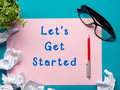 Let's get started message - Office desk table with supplies top view.  crumled paper, pen, glasses and flower. Royalty Free Stock Photo