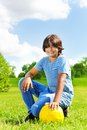 Let s play football portrait of years old happy smiling boy sit on squads with soccer ball on the field on bright sunny day Royalty Free Stock Photography