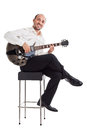 Let s play jazz a well dressed musician sitting on a stool and holding a guitar Stock Image