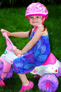 Let s ride a cute little toddler girl in a pretty blue sundress wearing a pink helmet sitting on a baby pink trike shallow depth Stock Photography