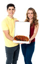 Lets share the yummy pizza young couple offering a medium sized delicious Stock Photo
