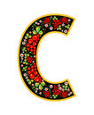 Letter C in the Russian style. The style of Khokhloma on the font. A symbol in the style of a Russian doll on a white background.