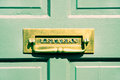 Letterbox an antique brass in a wooden front door Royalty Free Stock Image