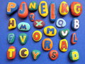 Letters pattern colorful painted on natural stone on blue background Royalty Free Stock Images