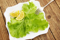 Lettuce fresh leaves of with lemon on a plate Royalty Free Stock Photography