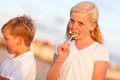 Leuke meisje en broer enjoying their lollipops Royalty-vrije Stock Foto's