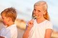 Leuke meisje en broer enjoying their lollipops Royalty-vrije Stock Foto's