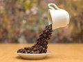 Levitating cup of coffee flowing beans beans pouring in a small plate on wooden table Royalty Free Stock Photography