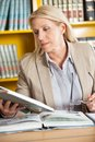 Librarian reading book at table in library female holding glasses while college Stock Photography
