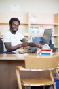 Librarian scanning books in library portrait of young male at desk Stock Images