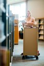 Librarian with trolley of books in library portrait confident female working Royalty Free Stock Photo