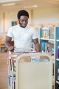 Librarian with trolley of books in library smiling male standing by shelves Stock Images