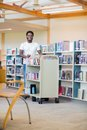 Librarian with trolley of books smiling in portrait african american bookstore Royalty Free Stock Photos