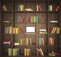 Library with wooden shelfs and multicolored books and laptop on the center shelf Stock Photo