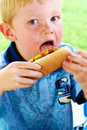 Licking mustard and ketchup young boy off of his hot dog Royalty Free Stock Photography
