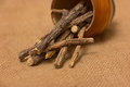 Licorice root sticks dried in a wooden pot on a burlap sack as a background Stock Images