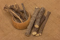 Licorice root sticks dried in a wooden pot on a burlap sack as a background Stock Photo