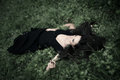 Lie in grass elegant woman long black dress full body shot Royalty Free Stock Images
