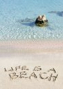 Life is a beach message written on white sand, with tropical sea waves in background Royalty Free Stock Photo