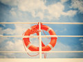 Life belt buoy red rescue ring on a ship against blue sky with clouds Royalty Free Stock Photo