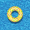 Life buoy floating in swimming pool. Beach rubber ring on water isolated on background. Lifebuoy, cute toy for children. Royalty Free Stock Photo