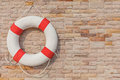 The life buoy is hanged on brick wall background nearby the swim Royalty Free Stock Photo