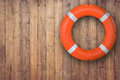 Life buoy hanging on wooden wall for emergency response when people sinking to water almost place near pool and beach. Royalty Free Stock Photo