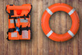 Life buoy and life jacket hanging on wooden wall for emergency response when people sinking to water,sea,pool. Royalty Free Stock Photo