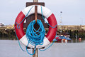 Life buoy on a post at a harbour red and white lifebuoy with blue rope Stock Photography