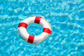 Life buoy red and white or saver floating in the blue water of a swimming pool Royalty Free Stock Images