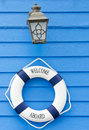 Life buoy welcome aboard sign and old lamp white blue with on blue wall Royalty Free Stock Photography
