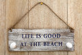 Life is good at the beach sign over oak wood background Stock Images