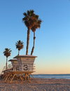 Life guard tower with palm trees as the sun sets in california Stock Images