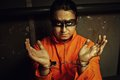 Life imprisonment handcuffed prisoner in orange clothes in his cell Stock Photo