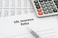 Life insurance policy with numbers calculator and pen on table Royalty Free Stock Images