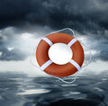 Life preserver an orange live or saver being tossed into water with a stormy cloudy background Stock Photos