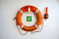 Life preservers on white wall life buoy on the deck of cruise ship a device made buoyant or inflatable material such as a jacket Stock Photos