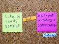 Life is simple famous confucius quote interpretation with sticker notes on cork board Royalty Free Stock Image