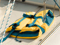 Life vest on a boat yellow saving with blue strips laying white yacht deck Royalty Free Stock Photo