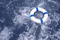 Lifebuoy lifebelt life saver rescue in a ocean storm full of f white foam Stock Photos